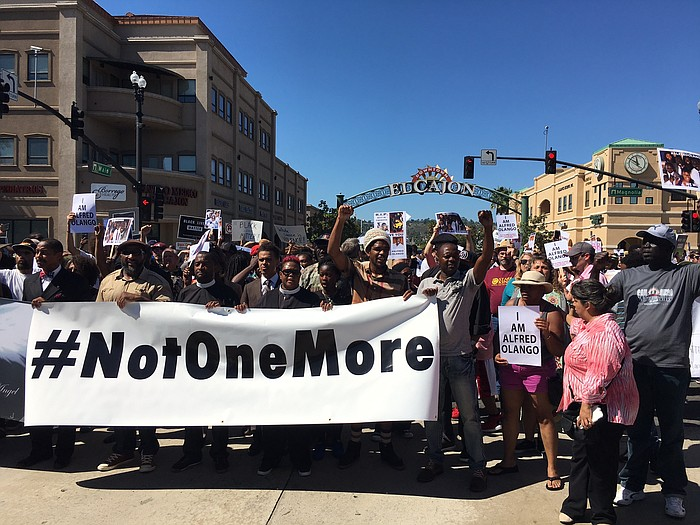 """Above: A crowd of several hundred demonstrators march peacefully down Main Street in El Cajon, Oct. 1, 2016. They carry signs that read """"Not One More"""" and """"I Am Alfred Olango."""" Police officers fatally shot Olango, a Ugandan immigrant living in El Cajon, Sept. 27, 2016. (Kris Arciaga/KPBS)"""