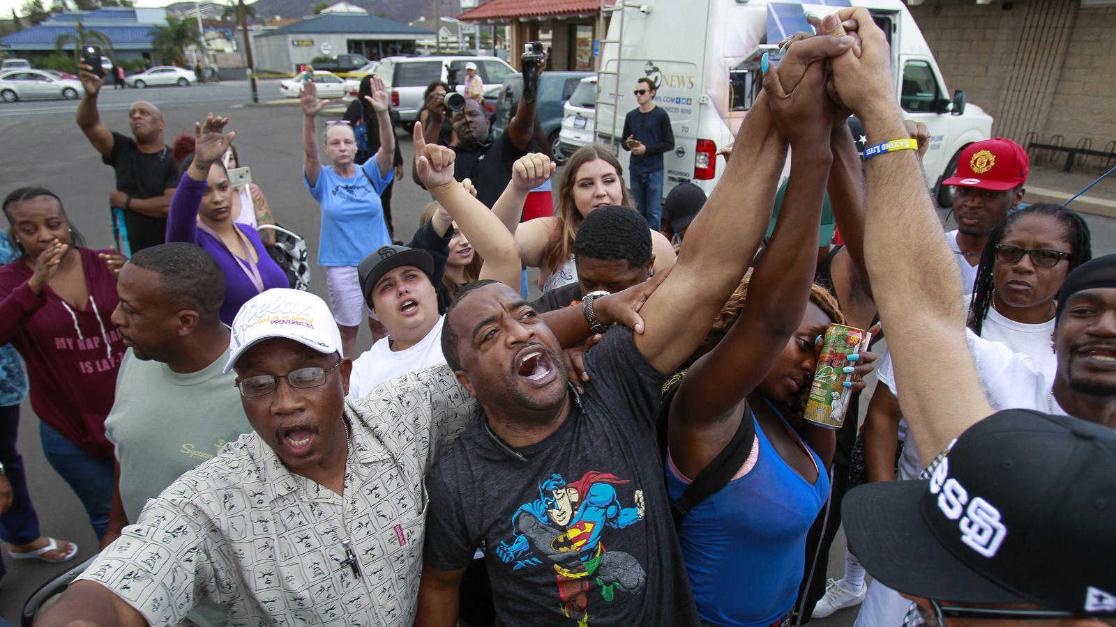 (Hayne Palmour IV / San Diego Union-Tribune. Pastor Russell Bowman, center, leads the crowd in a prayer at the scene where a black man was shot by El Cajon police earlier.