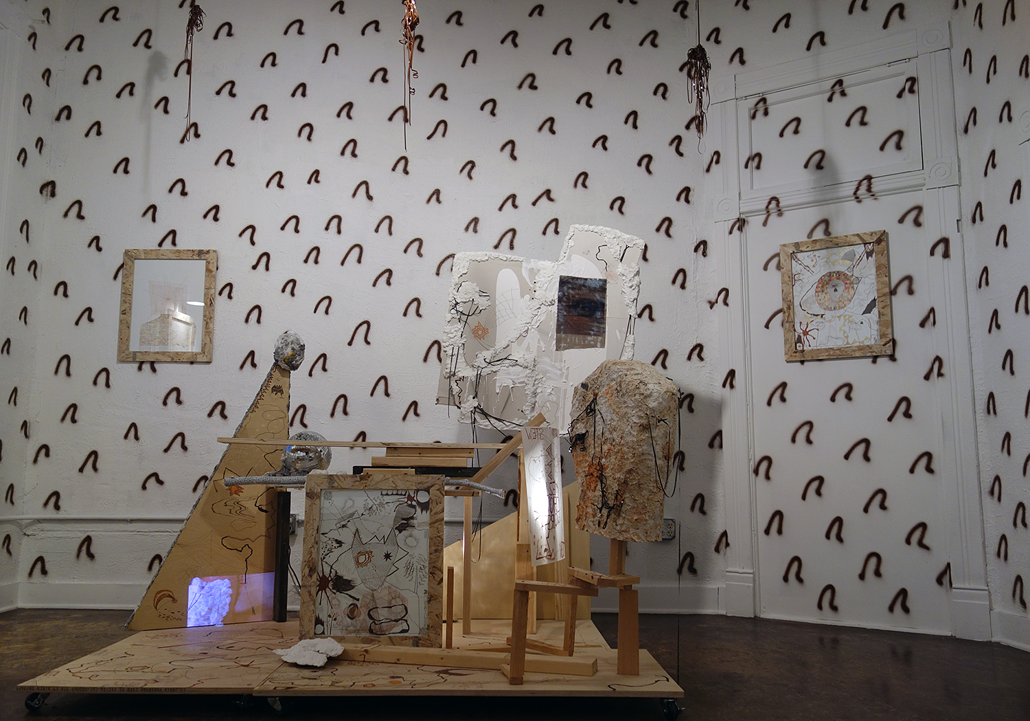 "anthony hawley // loculus // 2012-15 // installation // 71"" x 76"" x 52"" // media: wood, ink, paper-mache, cassette tape, plaster, foam, drywall, linen, inkjet print, thread, book-binding thread, disco balls, light, gesso, tree branch, pico projector, video projection, paper, duralar, wheels + hardware"