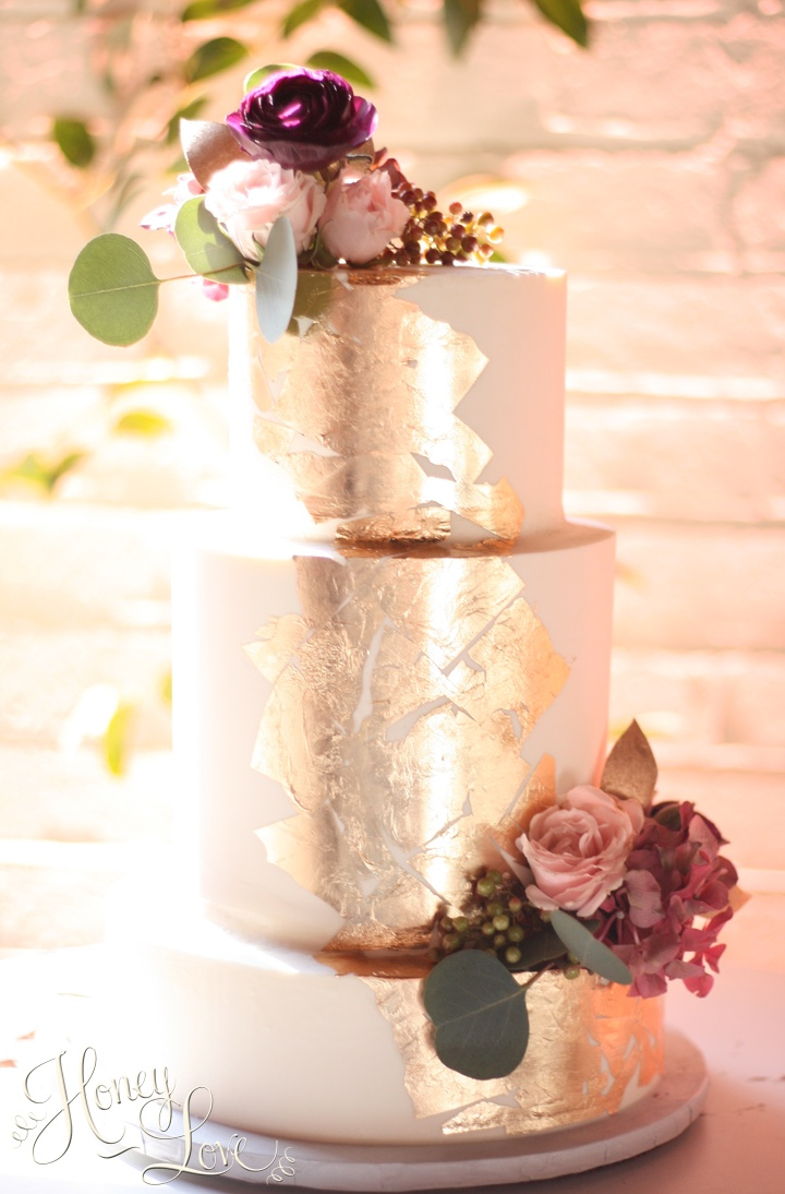 Buttercream wedding cake with gold leaf details, accented with fresh flowers.