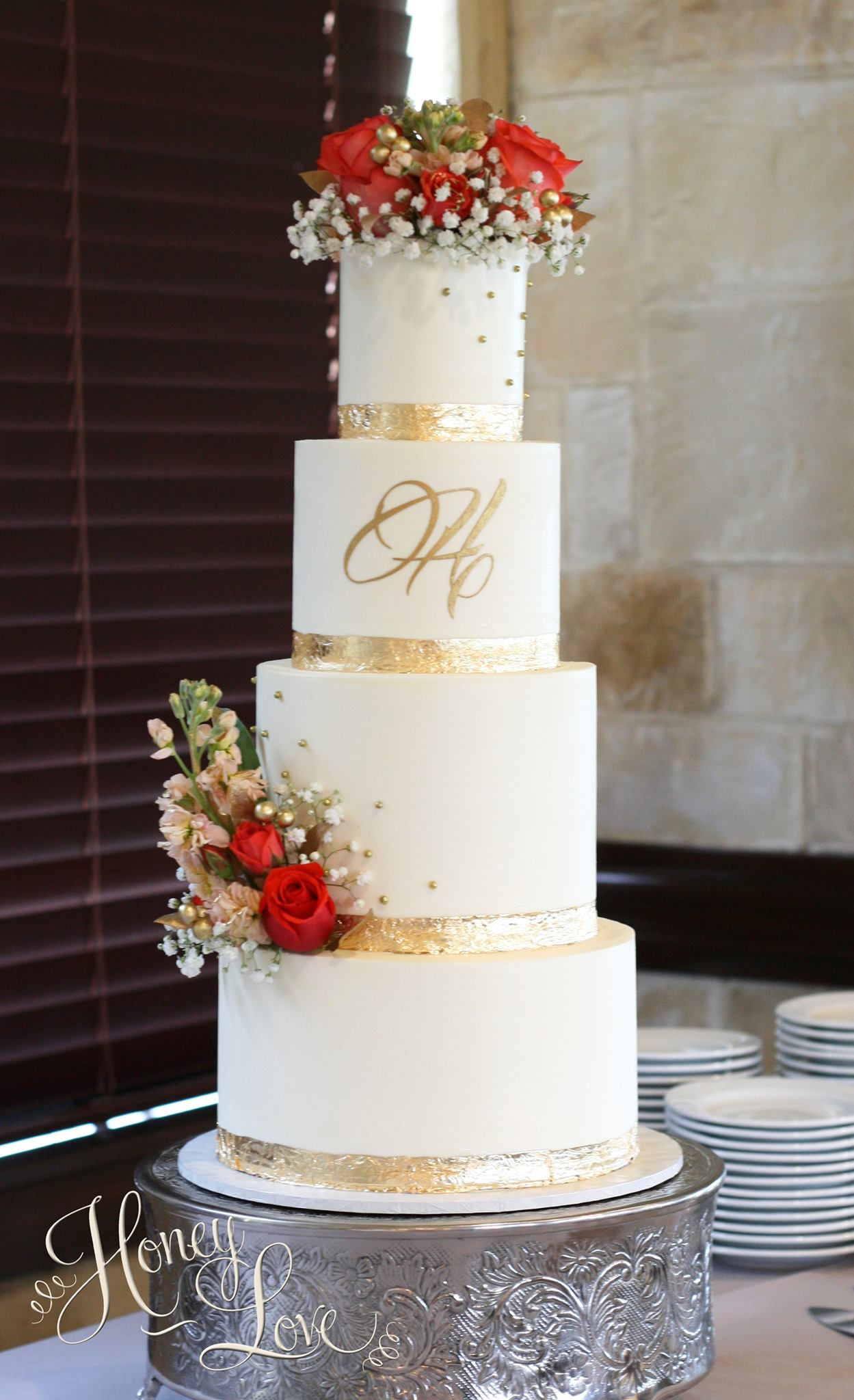 Buttercream wedding cake with gold leaf details and fresh flower accents.