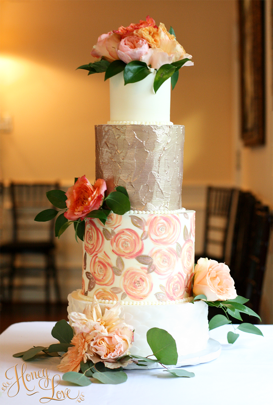 This buttercream wedding cake has a hand painted floral print and metallic accents. Wafer paper feathers adorn the bottom tier. Fresh flowers add the perfect pop of color.