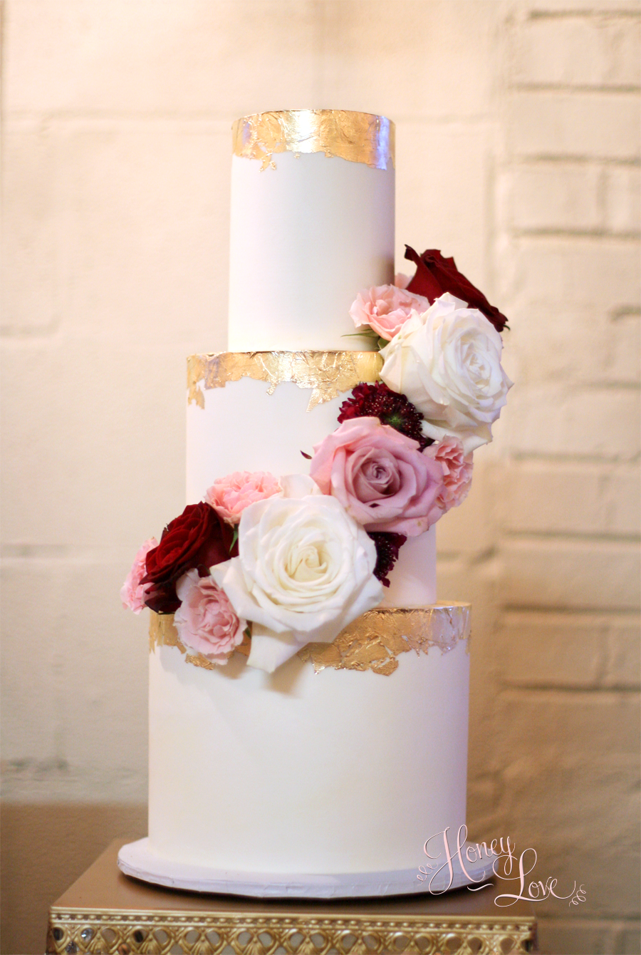 """This super smooth buttercream wedding cake is accented with edible gold leaf and fresh flowers. 8"""" 6"""" 4"""" with 3-layers per tier."""