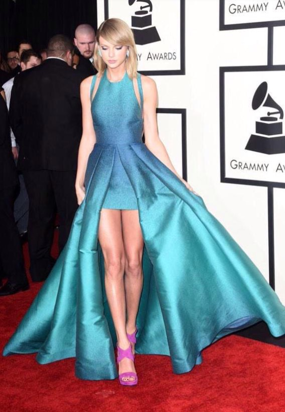 Taylor Swift turned it in a pop of color with an ombré turquoise ensemble and purple shoes. Love the look, but wished that she considered a matching clutch to round things off a bit.  **Lola's Notes** I honestly love this look. Clutch or not, this ensemble is pure beauty and perfect for Taylor (for all we know, there were pockets in that skirt!).