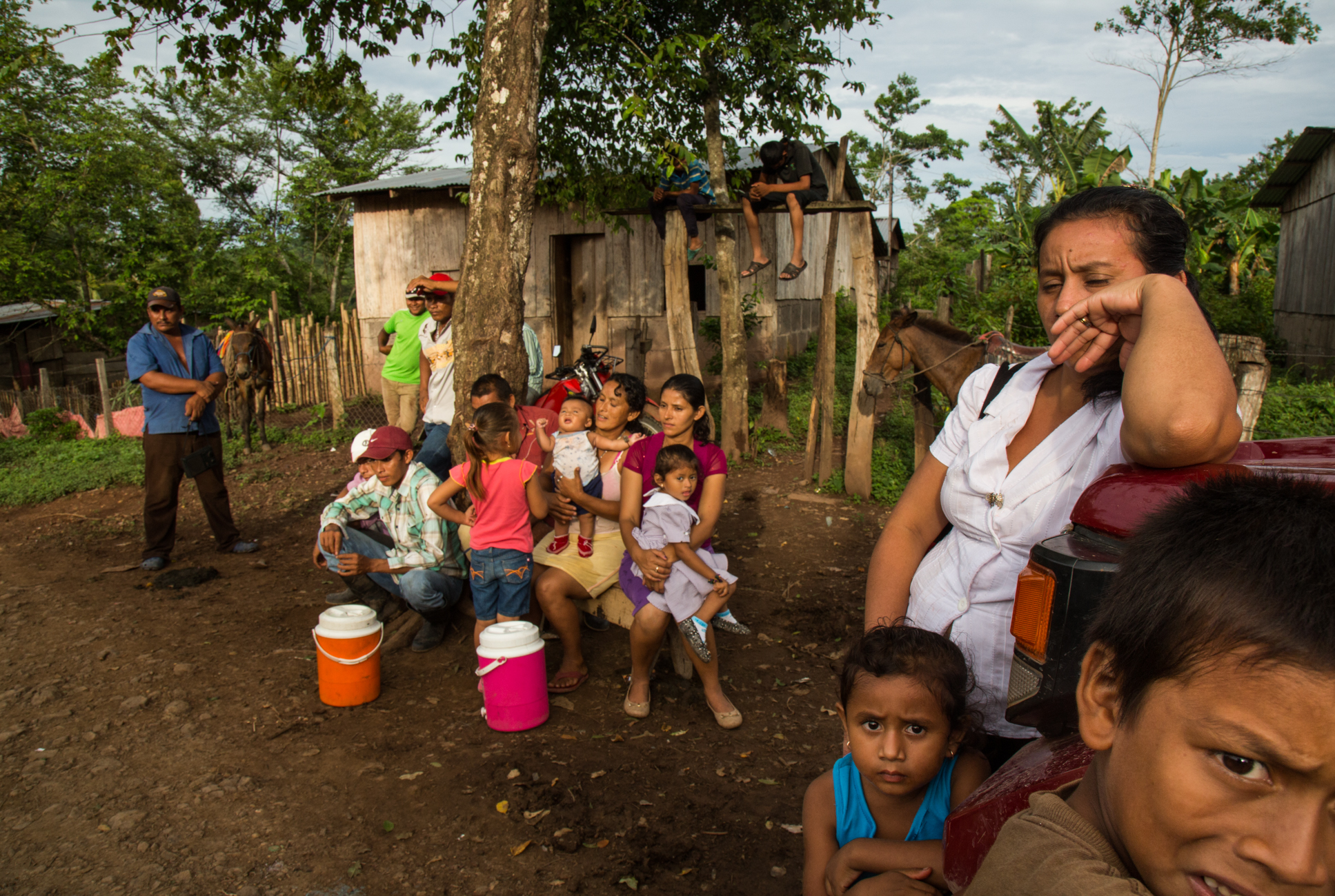 """Women and children sit quietly and listen to their husbands speaking with Francisca """"Chica"""" Ramirez as they discuss upcoming protest and potential forced displacement from their lands due to the Interoceanic Canal megaproject in El Roble, Rio San Juan, Nicaragua"""