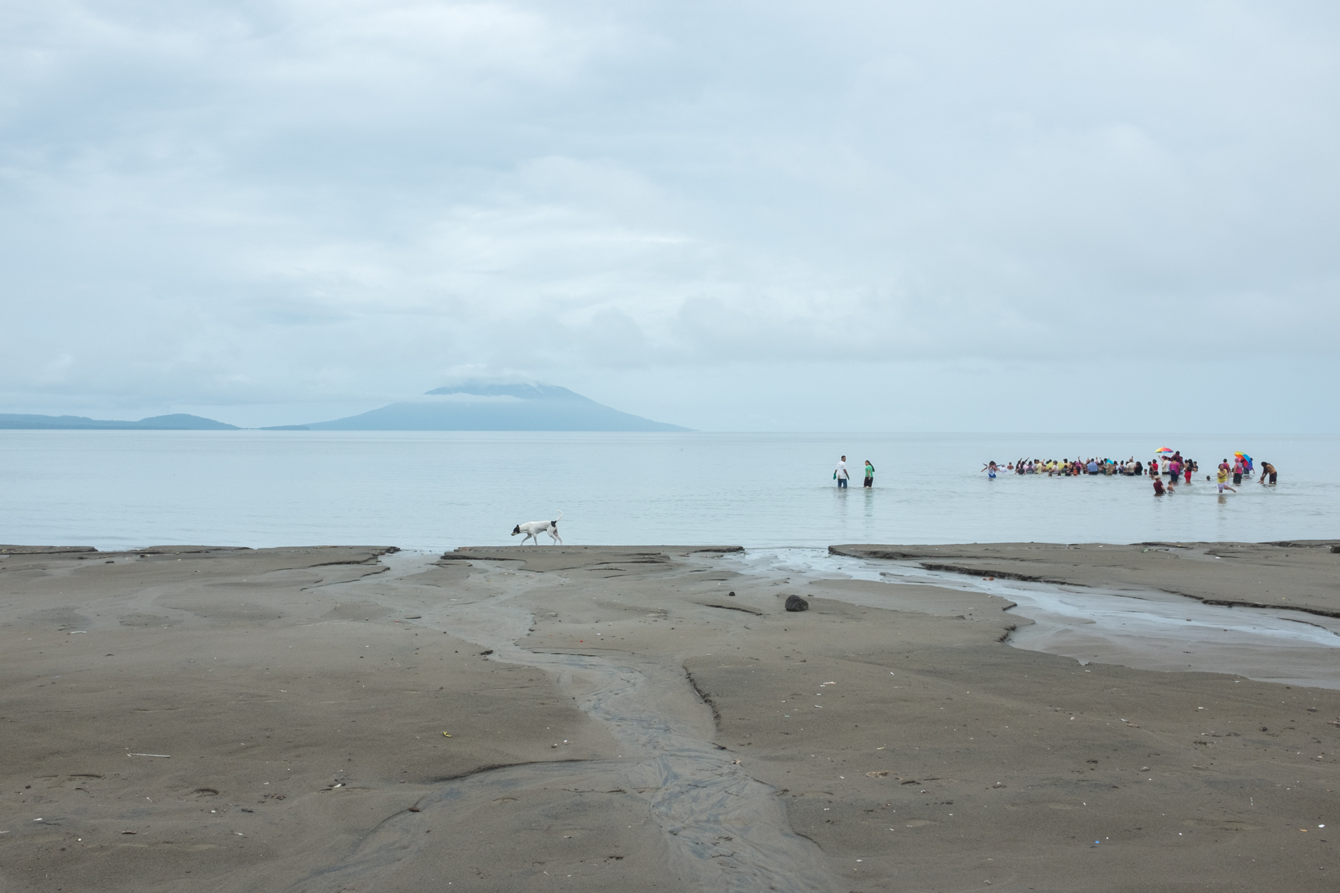 A babtism on the shores of Lake Nicaragua with the twin peaks of Ometepe Island in the distance near Rivas, Nicaragua