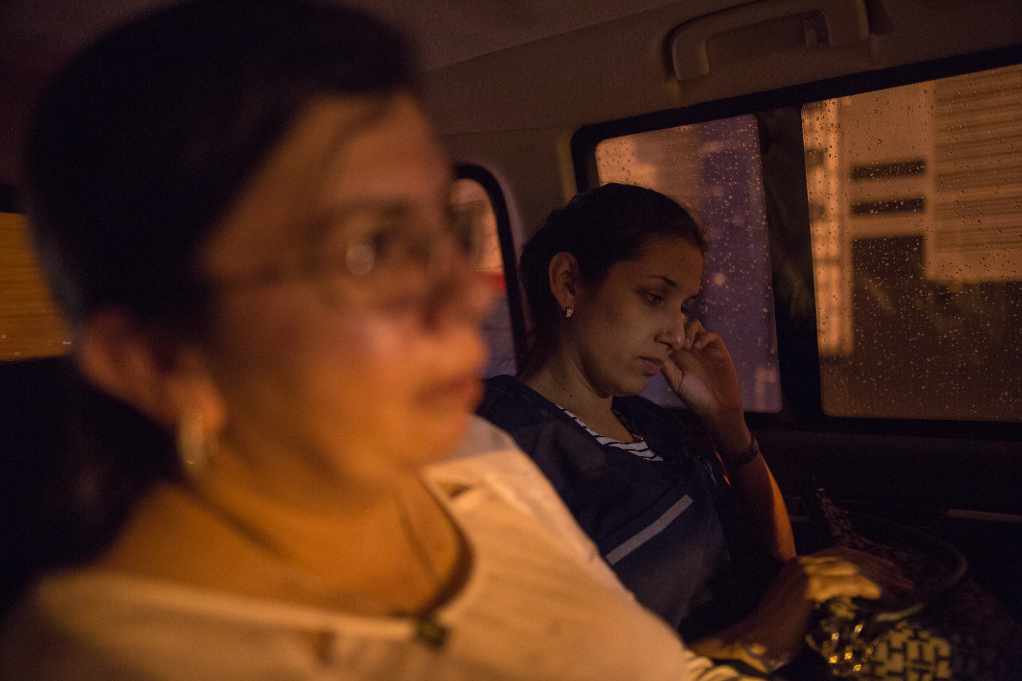 Julia Figueroa (left), human rights lawyer and leader of the CCALP, all women's legal collective, rides home with a young member of her collective in her state assigned bullet proof car after a syndicate meeting in Bucaramanga, Colombia. May 8, 2017.