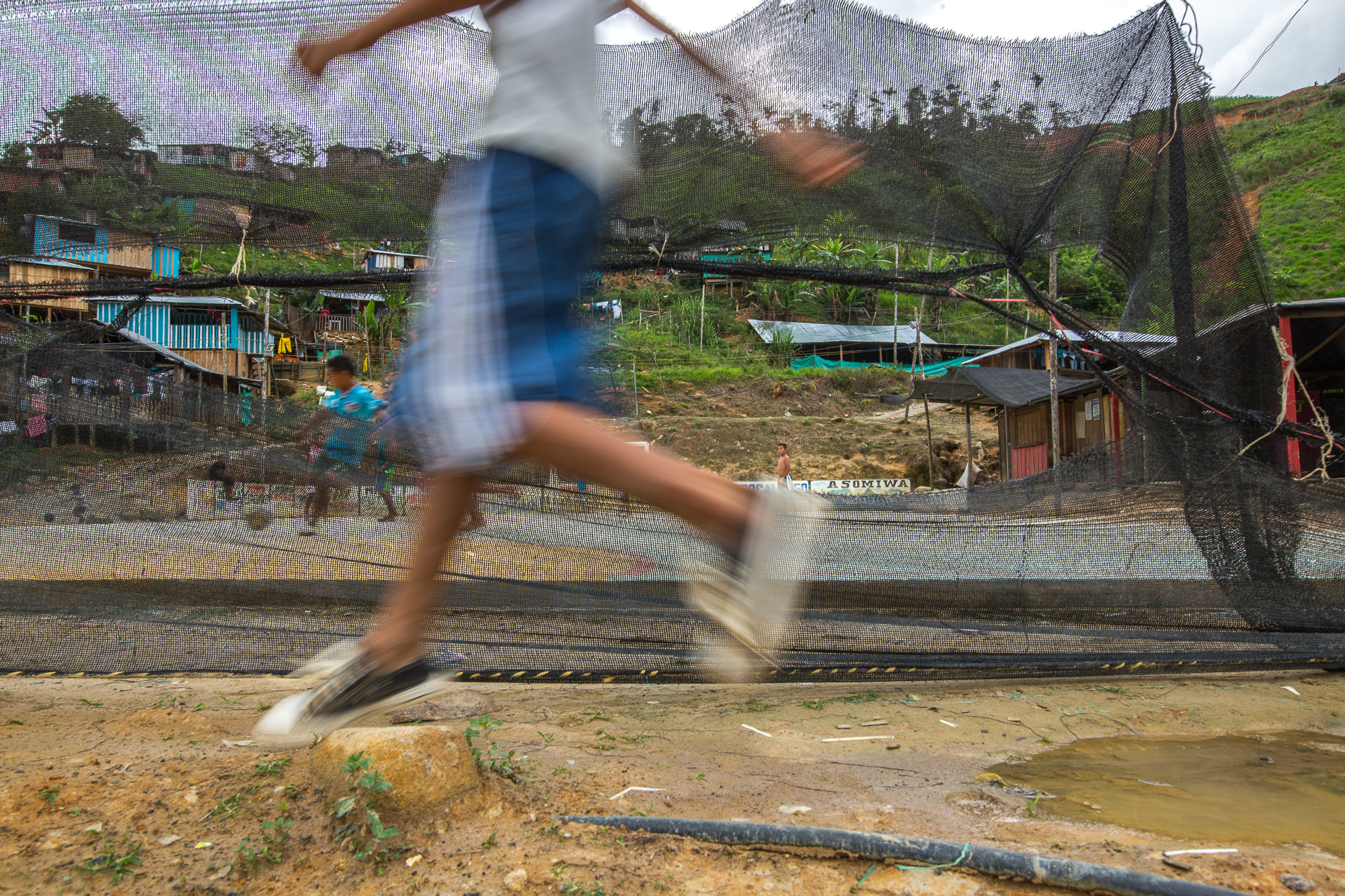 Kids play soccer on the court made by the mining companies and the ASOMIWA cooperative in the middle of the community. Mina Walter, Sur Bolivar, Colombia. May 12, 2017