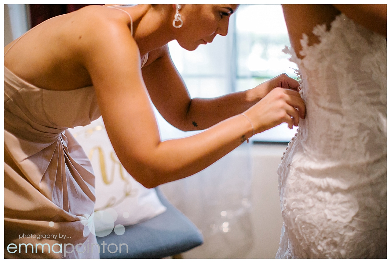 Bridesmaid getting bride buttoned up