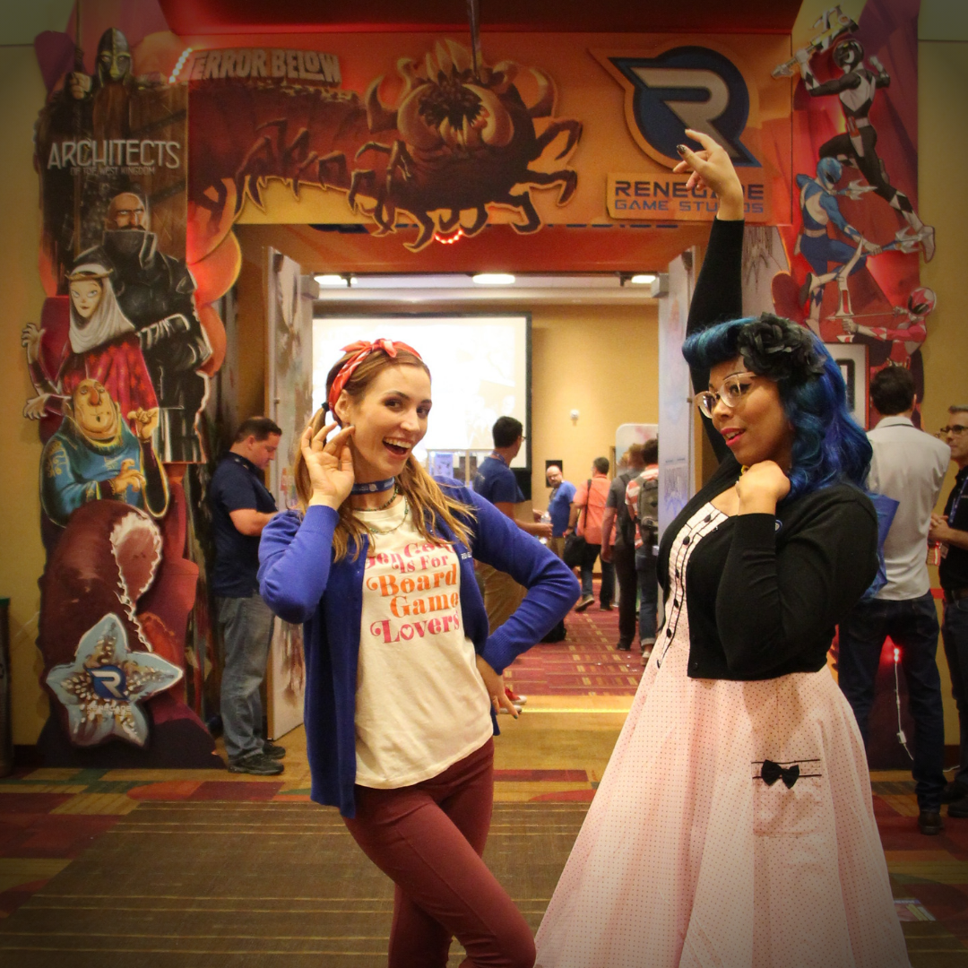 Mandi Hutchinson & Becca Scott in front of the Renegade Game Studios Event room