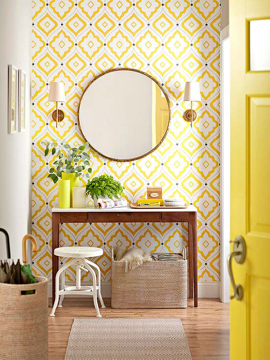 Brighten up your entry with a mirror, sconces a yellow door and some bright wallpaper. Image via  Centsational Girl