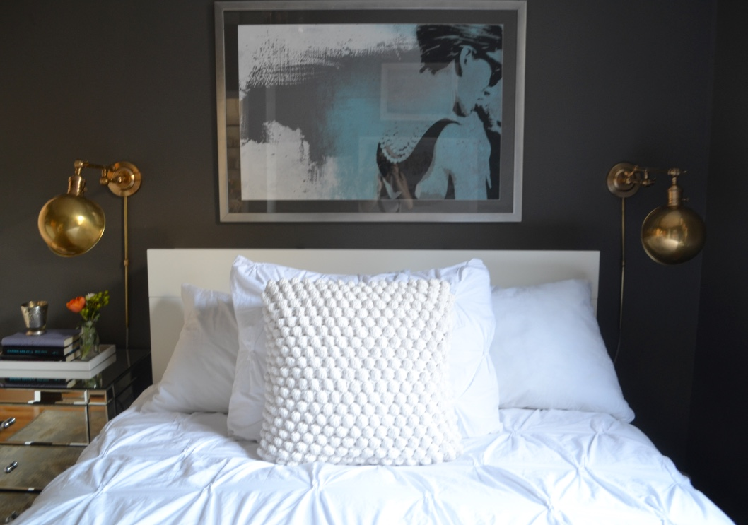 The all-white but textured bedding provides interest and the bedside sconces are not only functional and space-saving but also add a touch of shine.