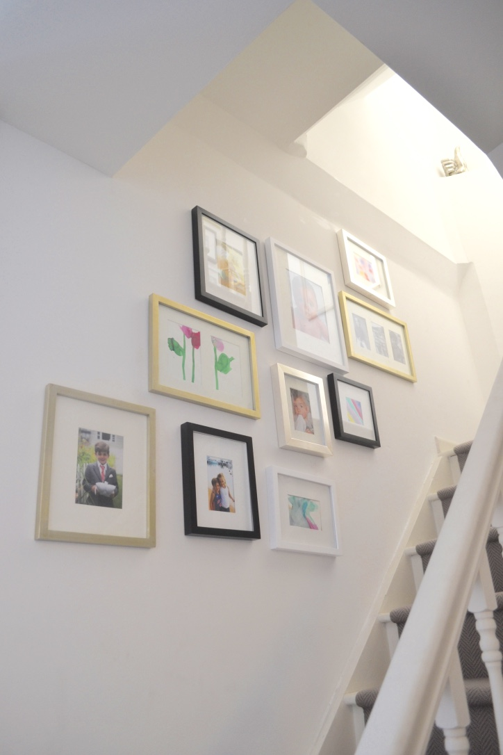 The use of black, white, silver and gold frames in different shapes and sizes provides an eclectic yet polished look.