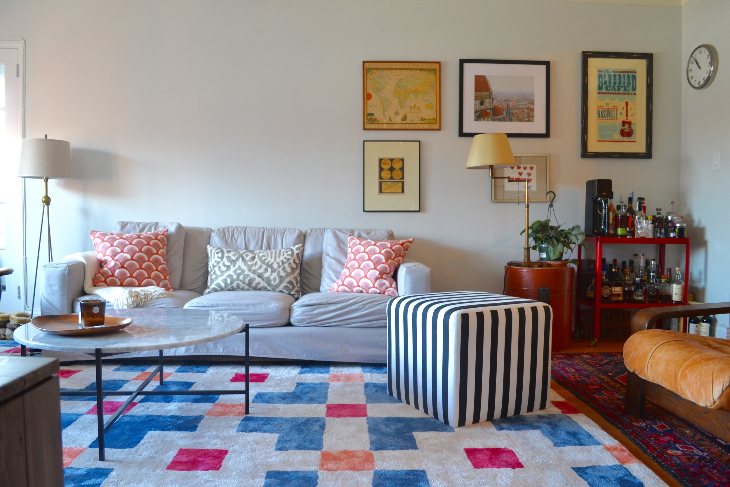 The slipcovered sofa is from Room and Board, the black and white cube is One Kings Lane. The area rug is from Anthropologie. The throw pillows were from fabrics Client Crafty and I picked out at Mood, and she sewed herself! The coffee table is a second hand find from AptDeco. The table lamp was a steal from Restoration Hardware Outlet.