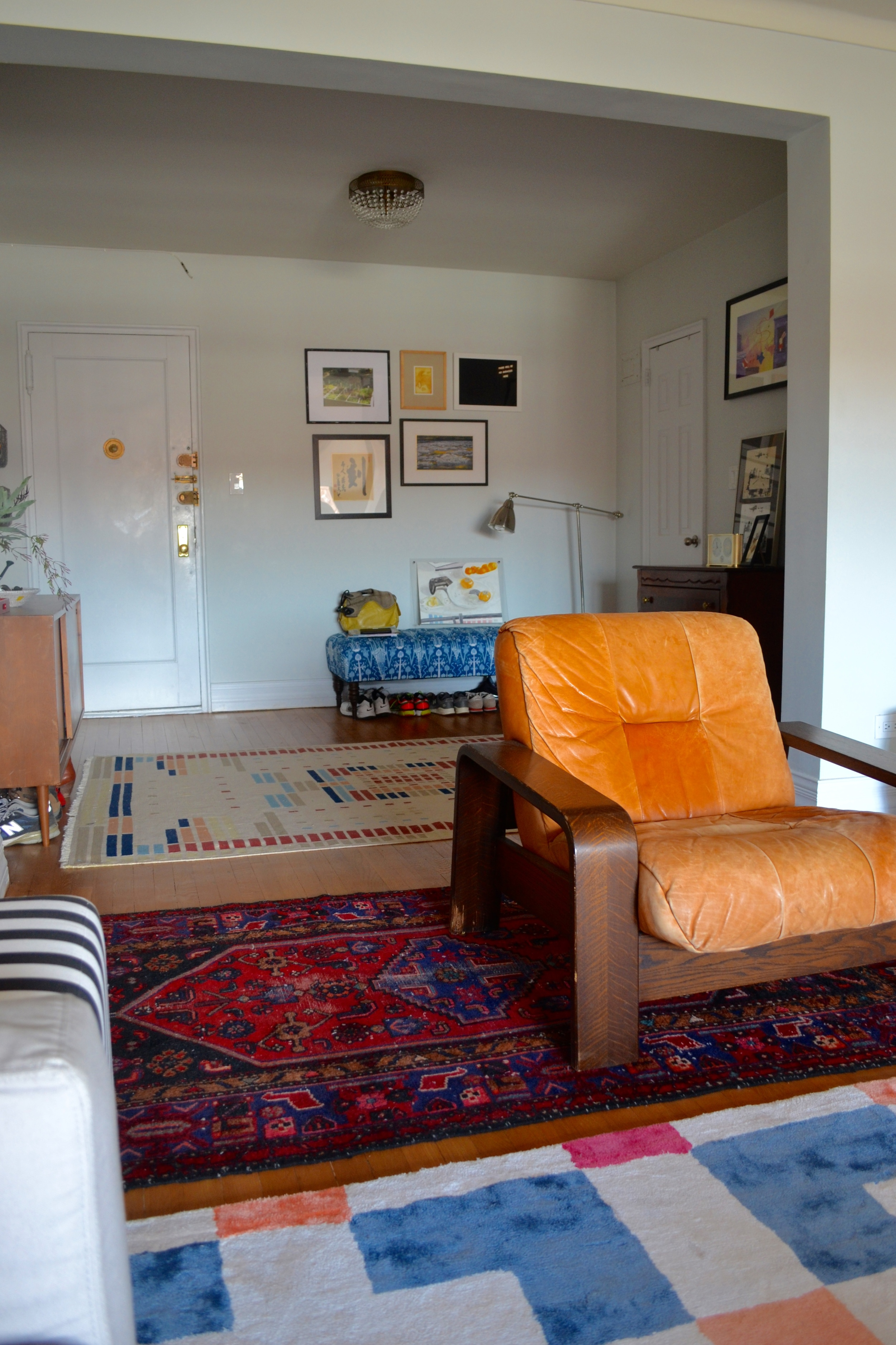 "We referred to the client's blue and red persian rug as the ""Rescue Rug"" throughout the project. Client Crafty and her boyfriend rescued it from a dumpster and had it professionally cleaned. Like new! It acted as the basis for our blue/red color scheme in the living and dining and is the perfect intermediary between the entry and living room rugs. The leather lounge chair was another craigslist find by Client Crafty."