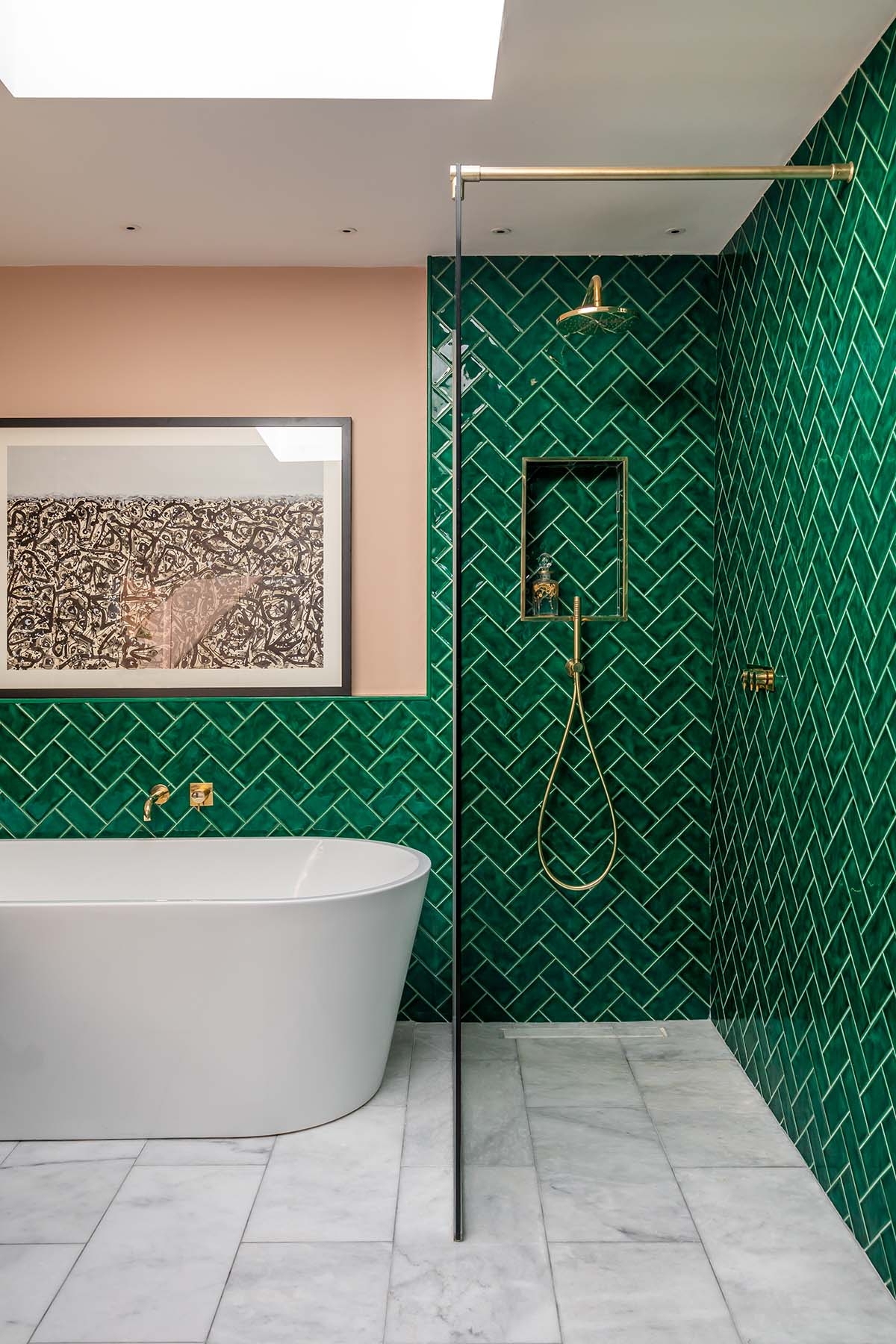 Use of Green in a Bathroom  It's a little unexpected in a bathroom, and that's what makes this stunning herringbone pattern tile so successful. Notice how the accent color of peach really makes the green pop along with the white and gives it a fresh modern feel, along with the gold modern fixtures.