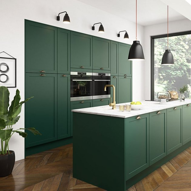 Use of Green in a Kitchen  Notice how the outside was brought in with this gorgeous green kitchen. The warmth of the herringbone floors and gold accents, along with clean simple lines, keep this green right on trend yet classic, and maintain the feeling of a clean and simple kitchen without the boredom factor.