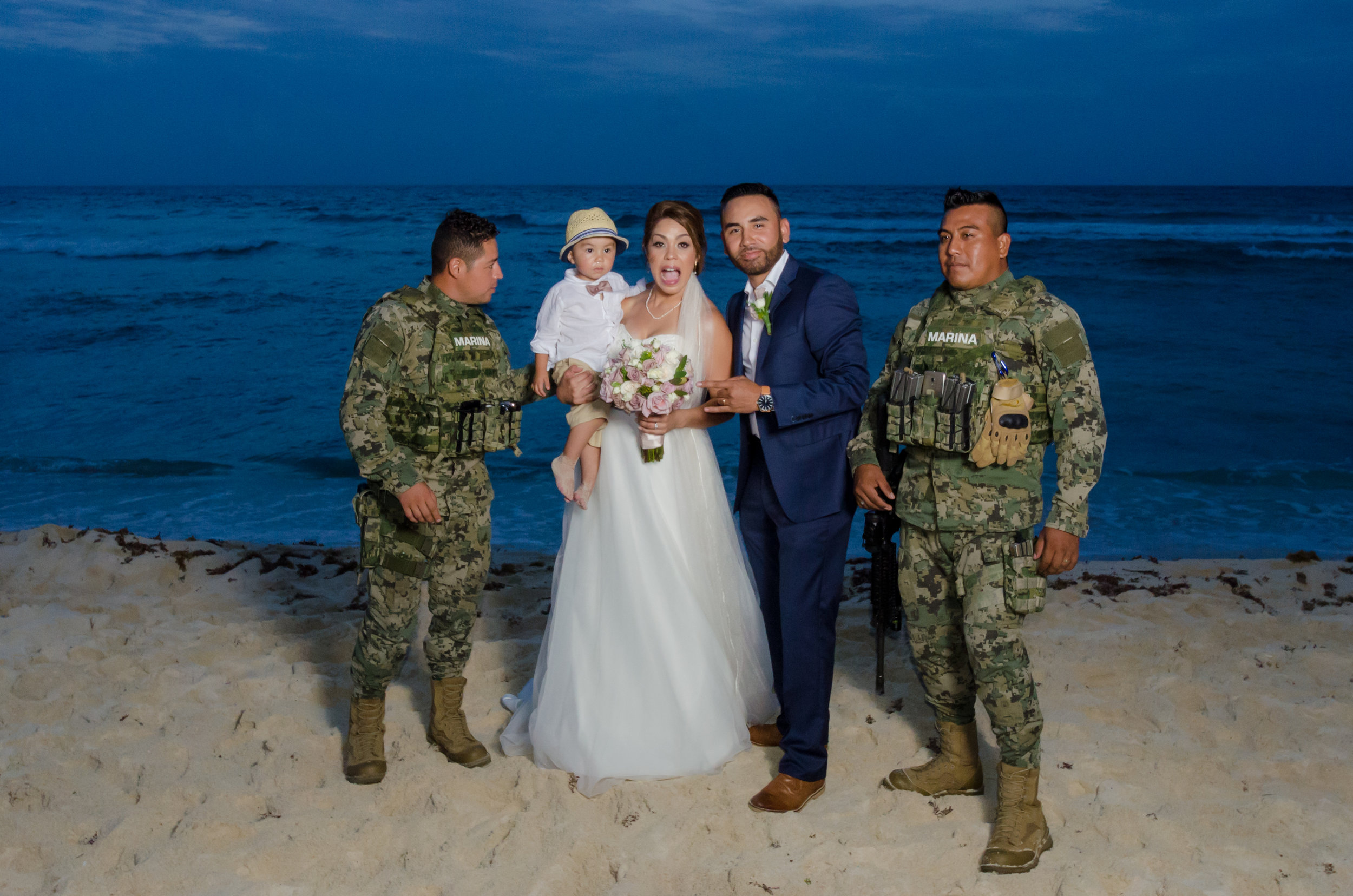 marines posing for a shot with bride and groom on the beach