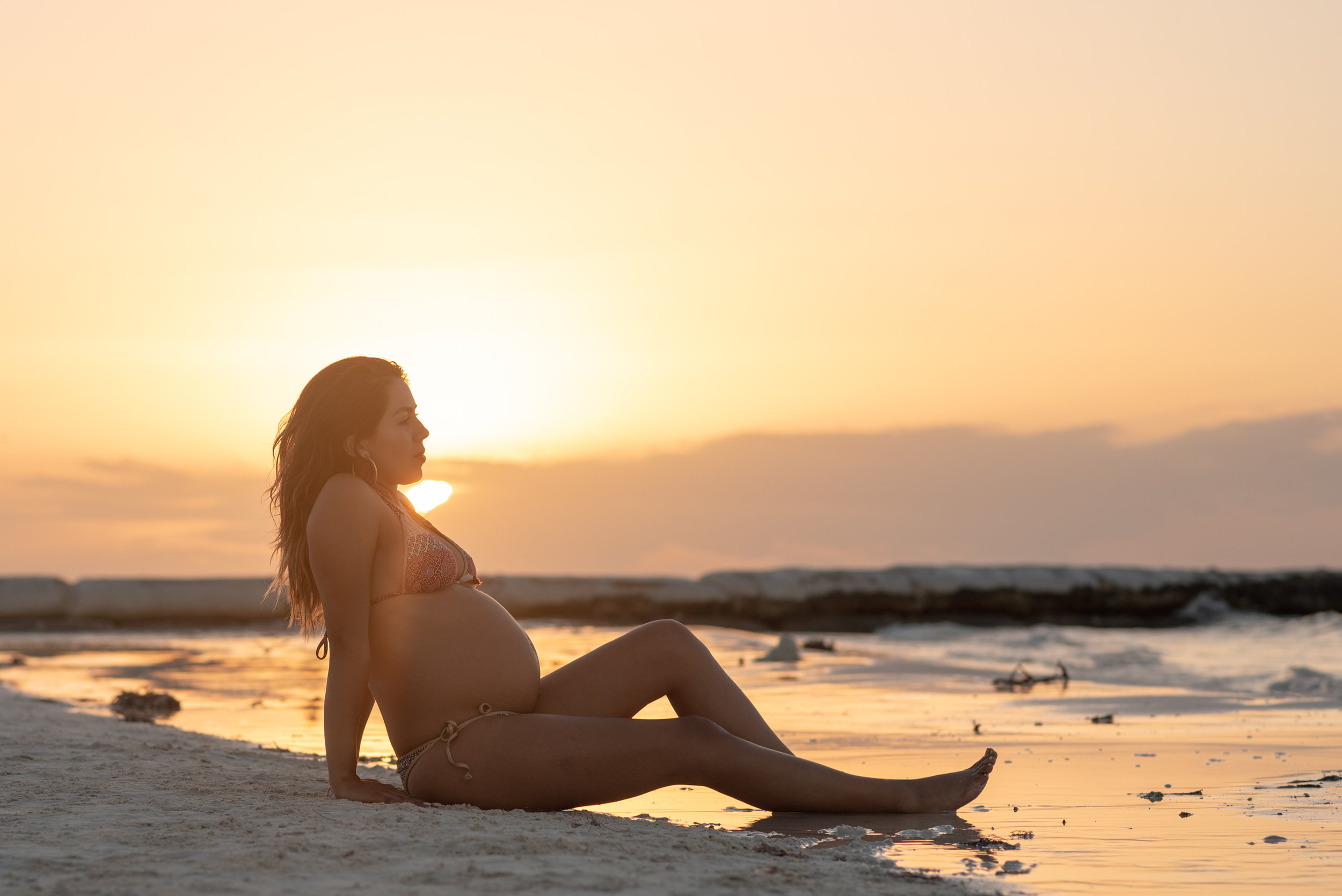 enjoying the pregnancy on the beach at sunset hour