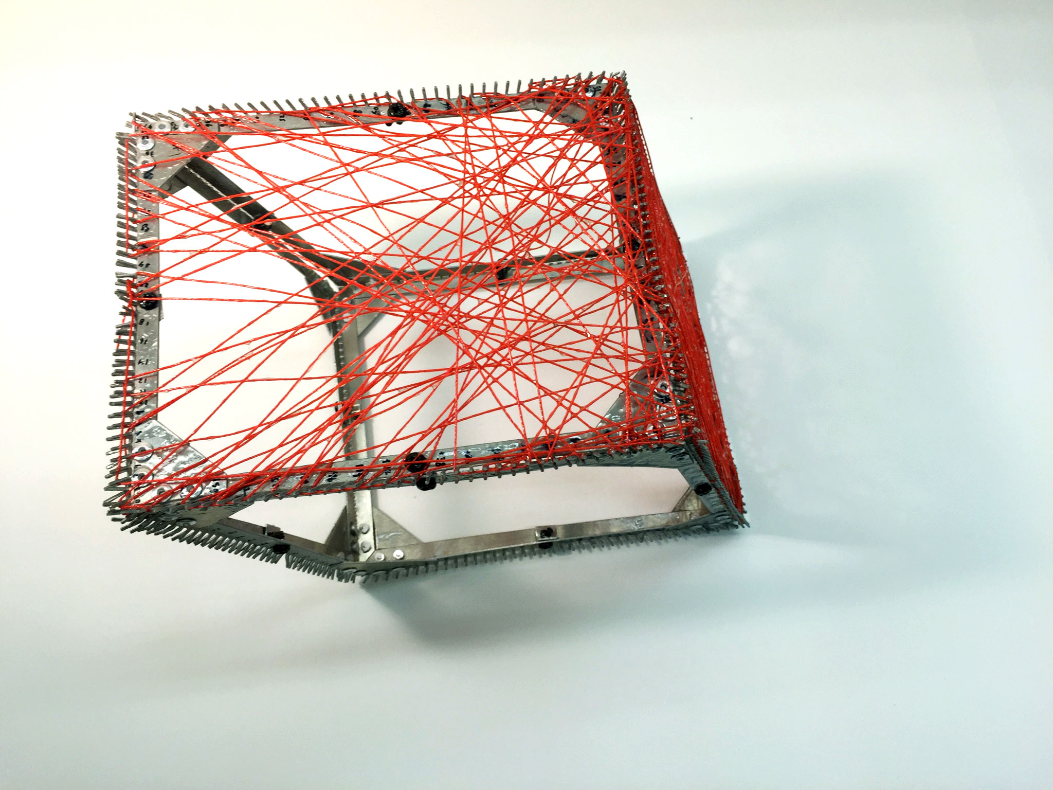 The second prototype served as a test for placing sting according to coordinates exported from the optimization Rhino model. To fabricate with the logic of straight line paths, a script was developed to create thousands of random lines from predetermined spacing along the frame edges. A filter was then applied to select lines stressed beyond a threshold. These lines were materialized with string hardened with resin.
