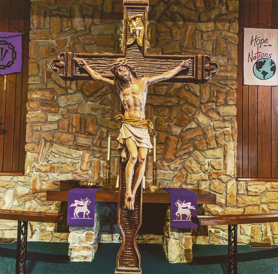 "This processional crucifix cross was blessed for use in our worship. It was purchased with the memorial funds from and in memory of Russ Cramm, Paul Erickson, Wayne Dunn and Val Dynes. This cross was also specifically made, upon request, for THIS congregation! It took a few months for us to receive it after ordering it because it was carved, by hand, for your eyes.  In the process of going through our worship today, I pray that we may answer a few question: 1) Why do we use a processional cross? To answer that, we use it on feast days, large festival days within the church year; Easter, Ascension, Pentecost, Trinity, Christmas, etc. The second question is this, ""Why do we have a crucifix? Why not an empty cross?"" For this question, I will allow the worship service itself to give the answers.  But, to be sure, we do not hold any superstitious fantasies about a piece of wood on which our Lord may or may not have actually been crucified – any more than we hold any superstitious thoughts about the cross on our altar or the cross I wear around my neck or the cross jewelry we wear. These are only 'symbols. And the purpose of 'symbols' is to point to something beyond themselves, and not to the thing itself.  It's not the cross itself that we worship and adore – but all that the cross points to – which is the indescribable love of the almighty God that He was poured out onto this fallen, corrupt and sinful world through His perfect, innocent, holy Son, who suffered the punishment that we deserve, by bearing them in His body unto death, even death on a cross."