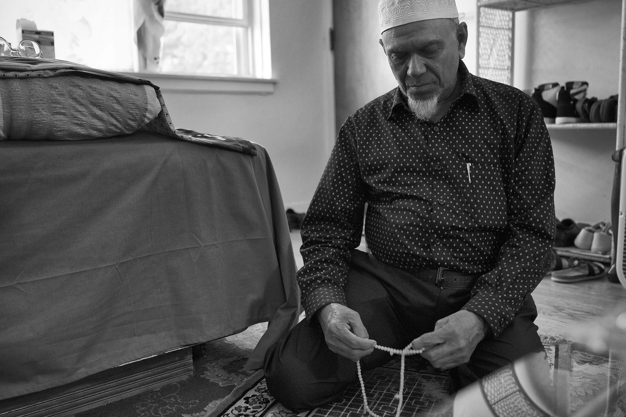"Mohammed pays in his living room.  Since the United States offered him citizenship, he views the US as his country.  ""When I pray, it's to protect the US government – for peace here and unity.  This is the most at-home I've felt."""