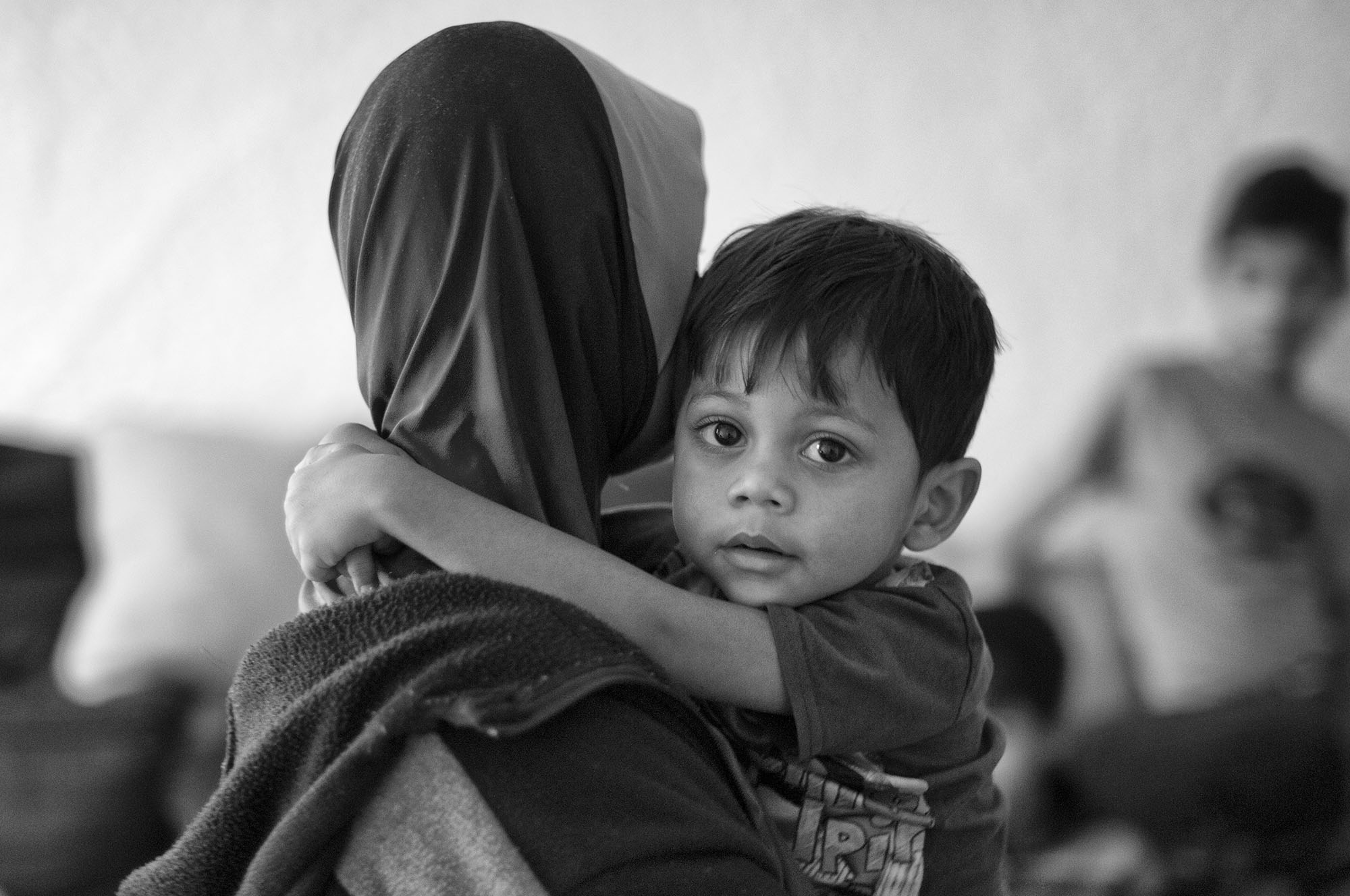 Mohammed Sultan, a three-year-old Rohingya boy, clings to his mother in a neighbor's home.  Mohammed was born in a refugee camp in Bangladesh.