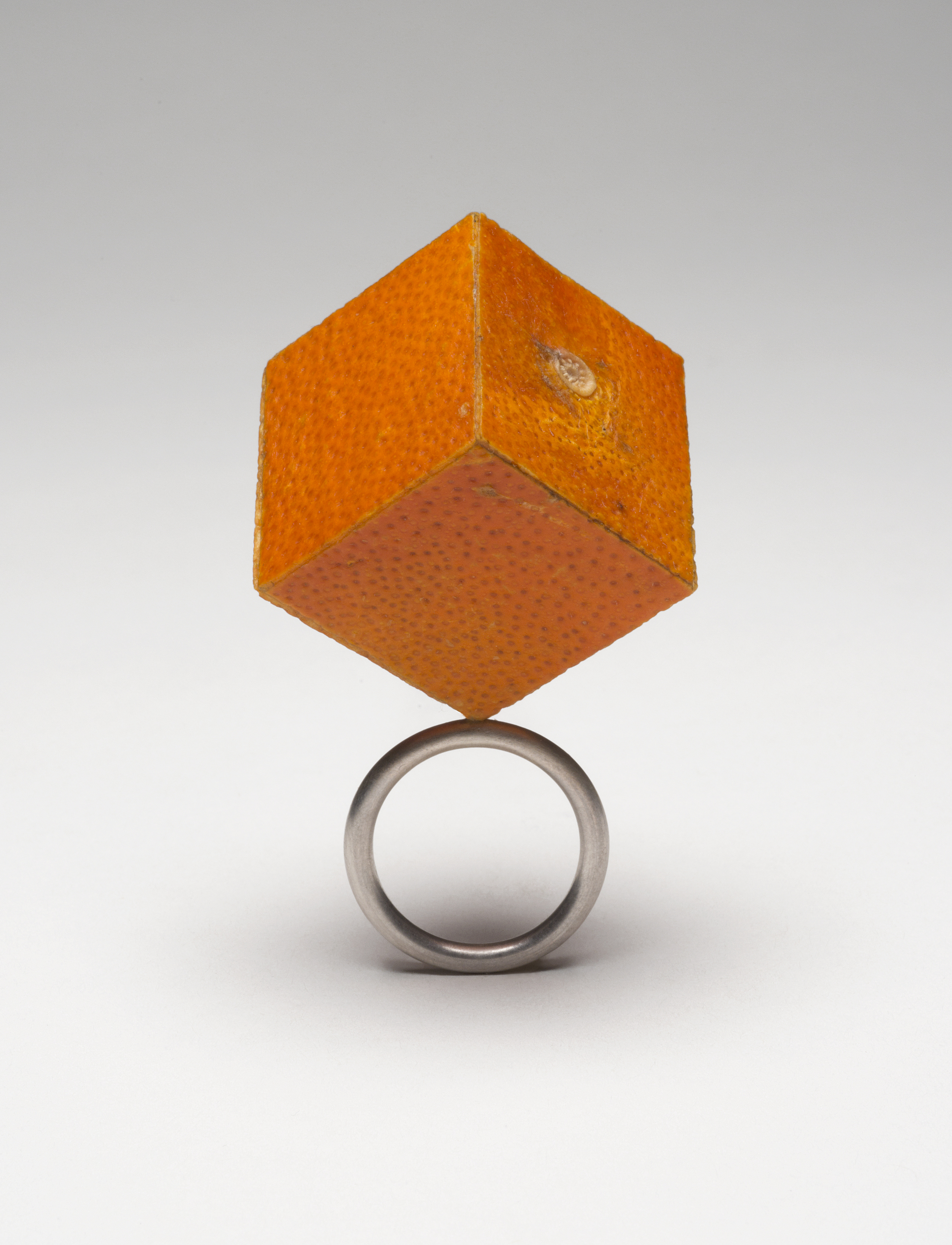 "One Inch Cubic Tangelo Ring , 2015. Tangelo peel, plywood, sterling silver. 2.25"" x 1.5"" x 1.5"""