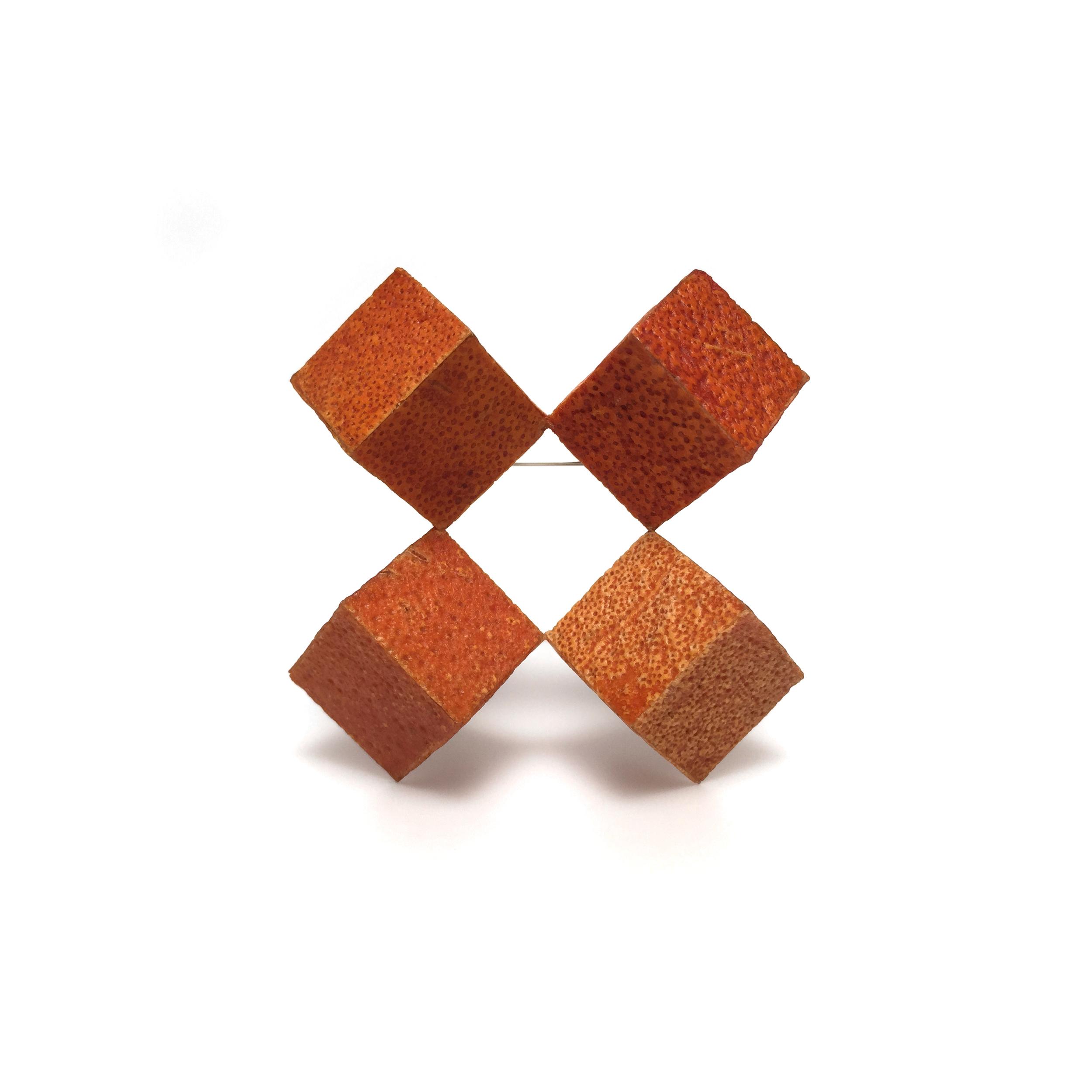 "Cubic Tangelo Brooch III , 2015. Tangelo peel, plywood, steel. 2.5"" x 2.5"" x 1.25"""