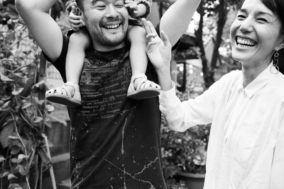 A picture of a mother and a father smiling with a little boy on the father's shoulders.