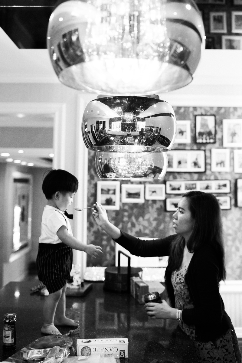 A mother feeds her son while he stands on the counter during a family photoshoot in Kuala Lumpur.