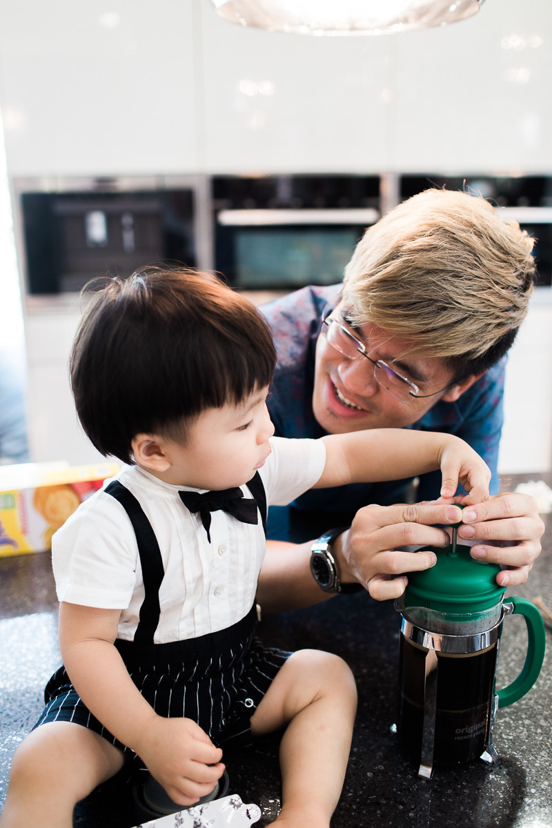 A father and his son make coffee with a french press during an in home family photoshoot.