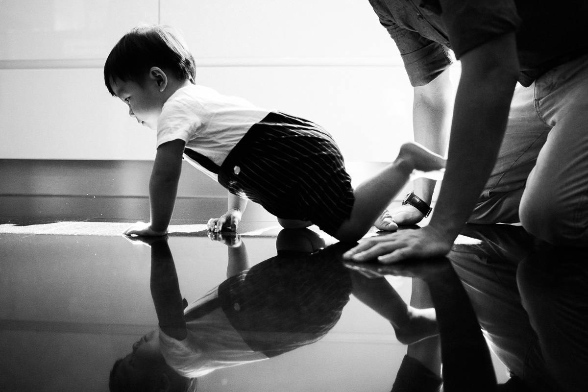 A black and white images of a father crawling with his son at home in Kuala Lumpur.