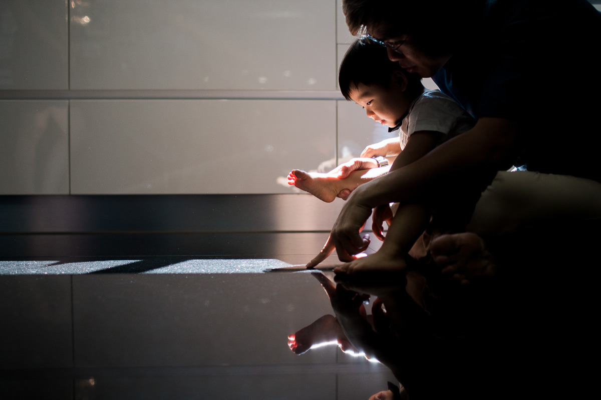 A father and his toddler son play in reflective light at home in Kuala Lumpur.