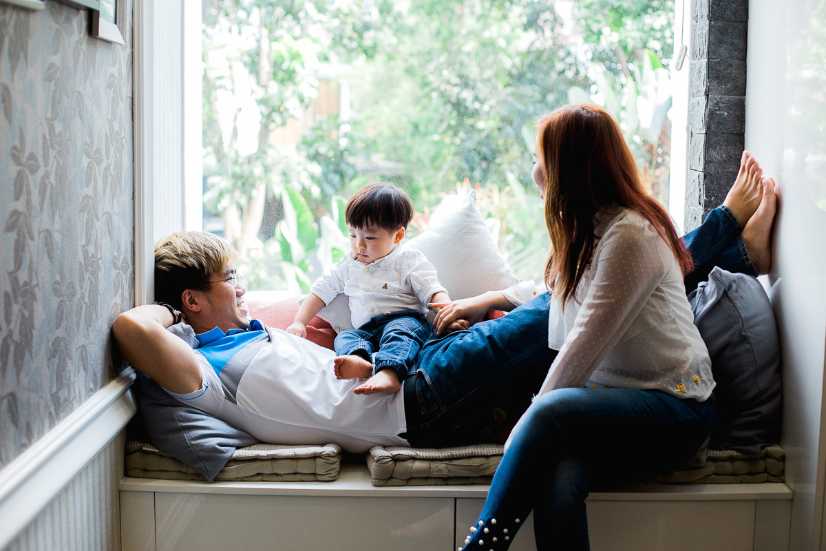 A lifestyle family photoshoot featuring a young family and their toddler son lounging in a window seat, at home in Kuala Lumpur.