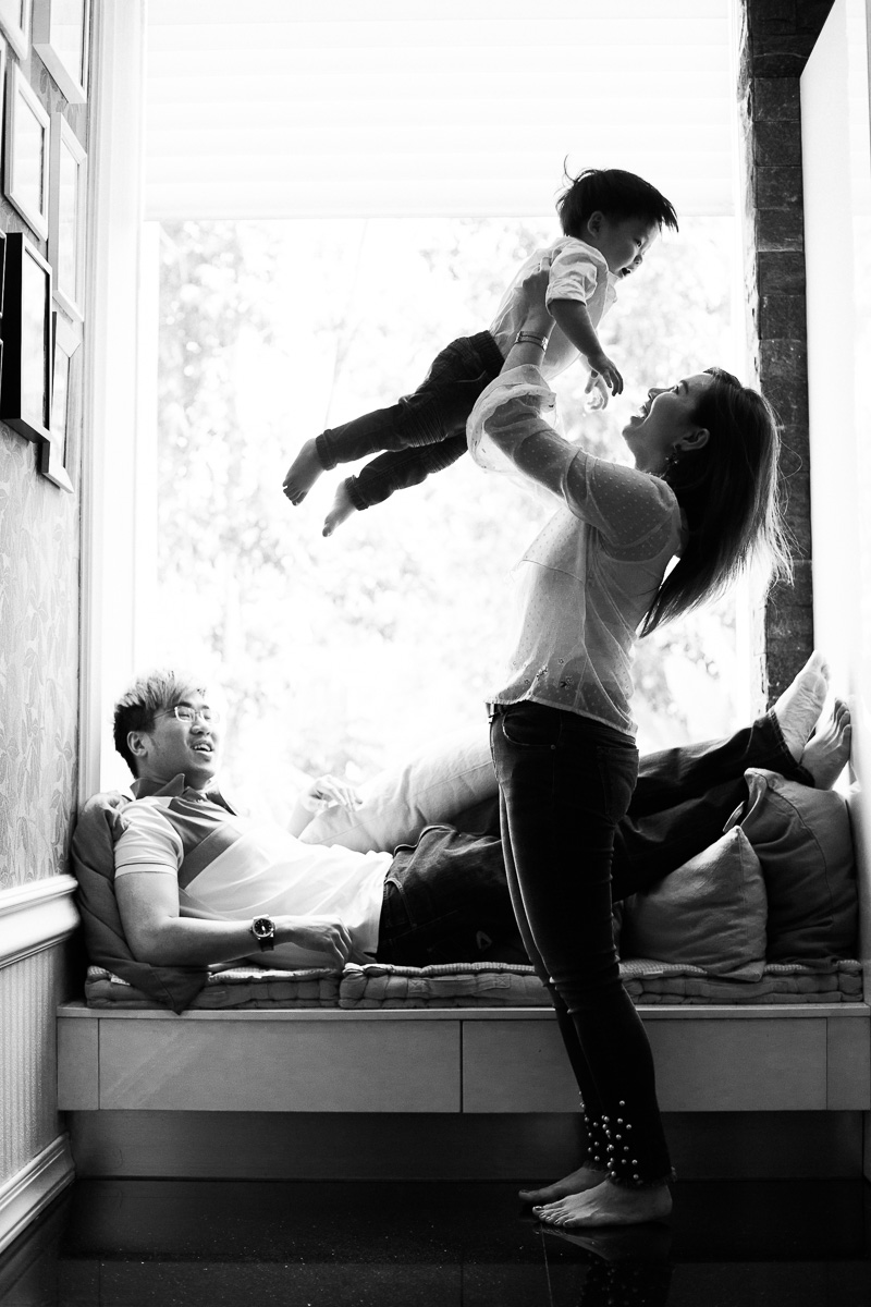 A mother plays with her toddler son by lifting him overhead while a father looks on and smiles by family photographer Erica Knecht.