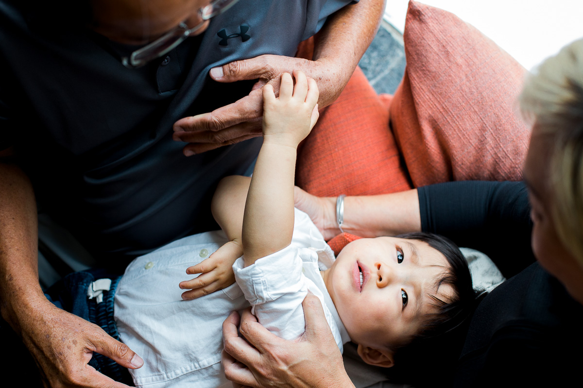 Grandparents embrace a young boy who looks up into his grandmother's eyes during a family photoshoot in Kuala Lumpur.