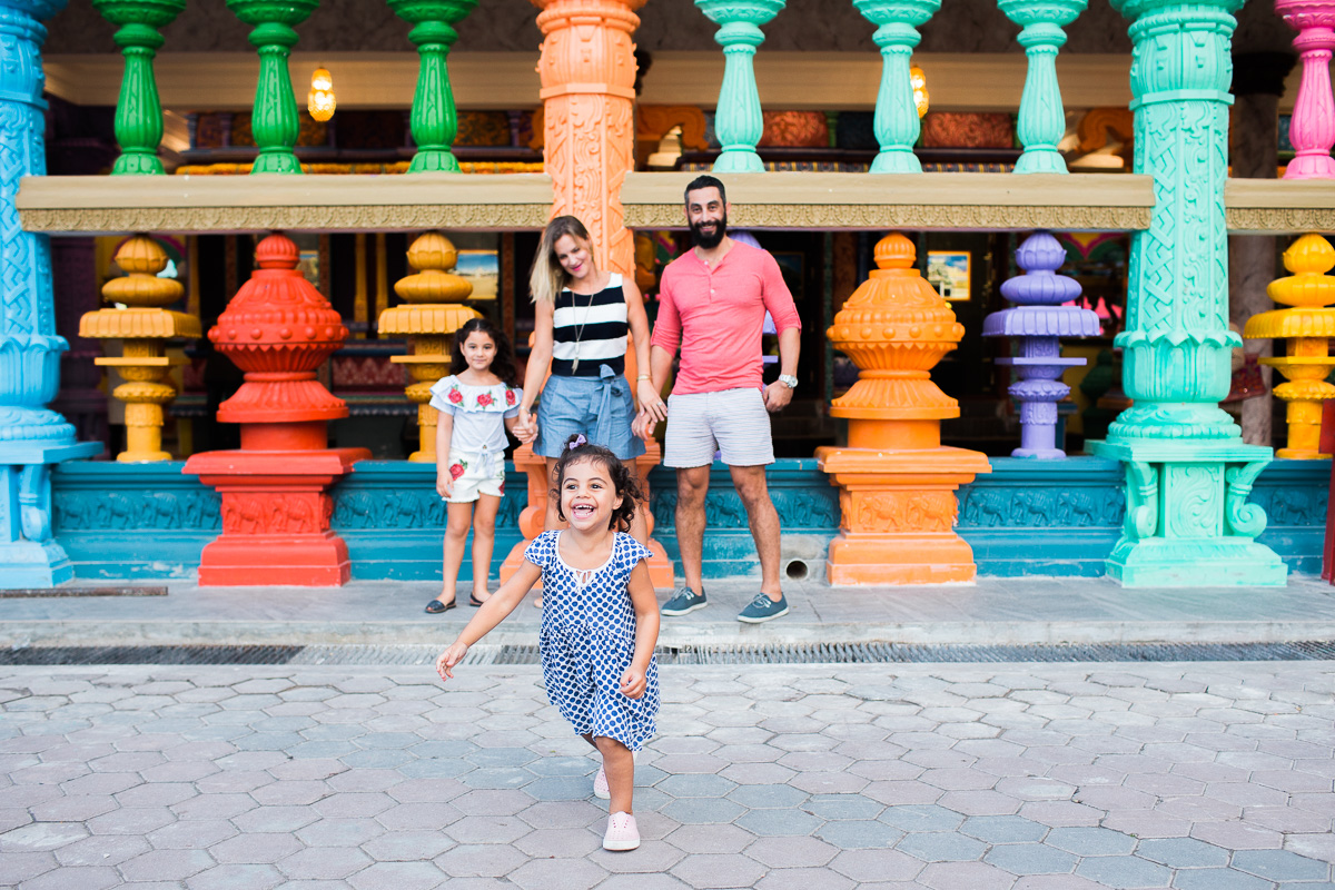 A family stands together as their little girl runs towards the camera with an exuberant smile on her face at Batu Caves.
