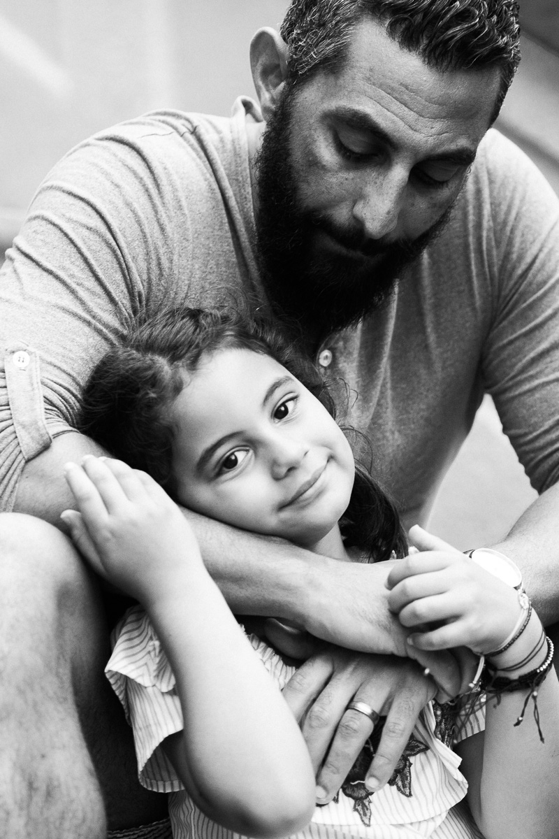 A black and white portrait of a father embracing his daughter in Kuala Lumpur.