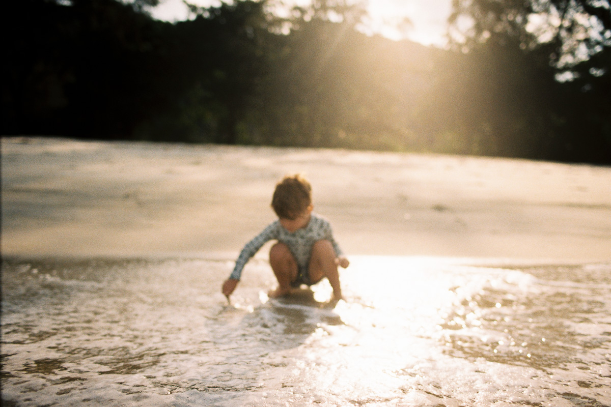 a boy plays in the sand at sunset on Kuantan Beach by Kuala Lumpur family photographer erica knecht