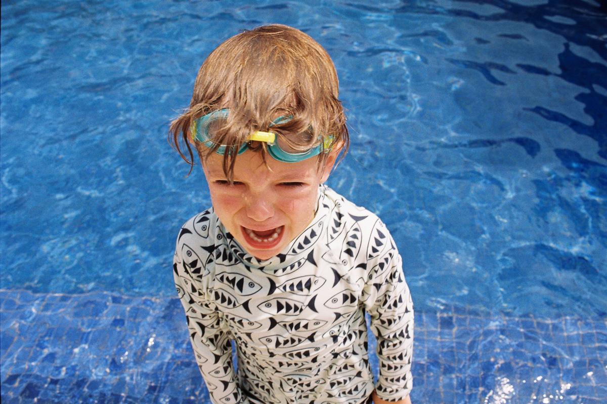 a boy cries in the pool - kuantan - 35 mm film - kodak gold - kuala lumpur photographer erica knecht
