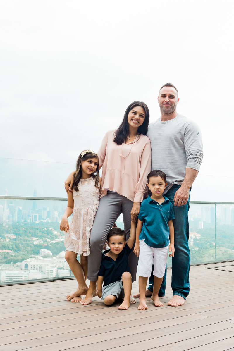A beautiful multi-ethnic family gather's together with a view of the Kuala Lumpur skyline by lifestyle photographer Erica Knecht