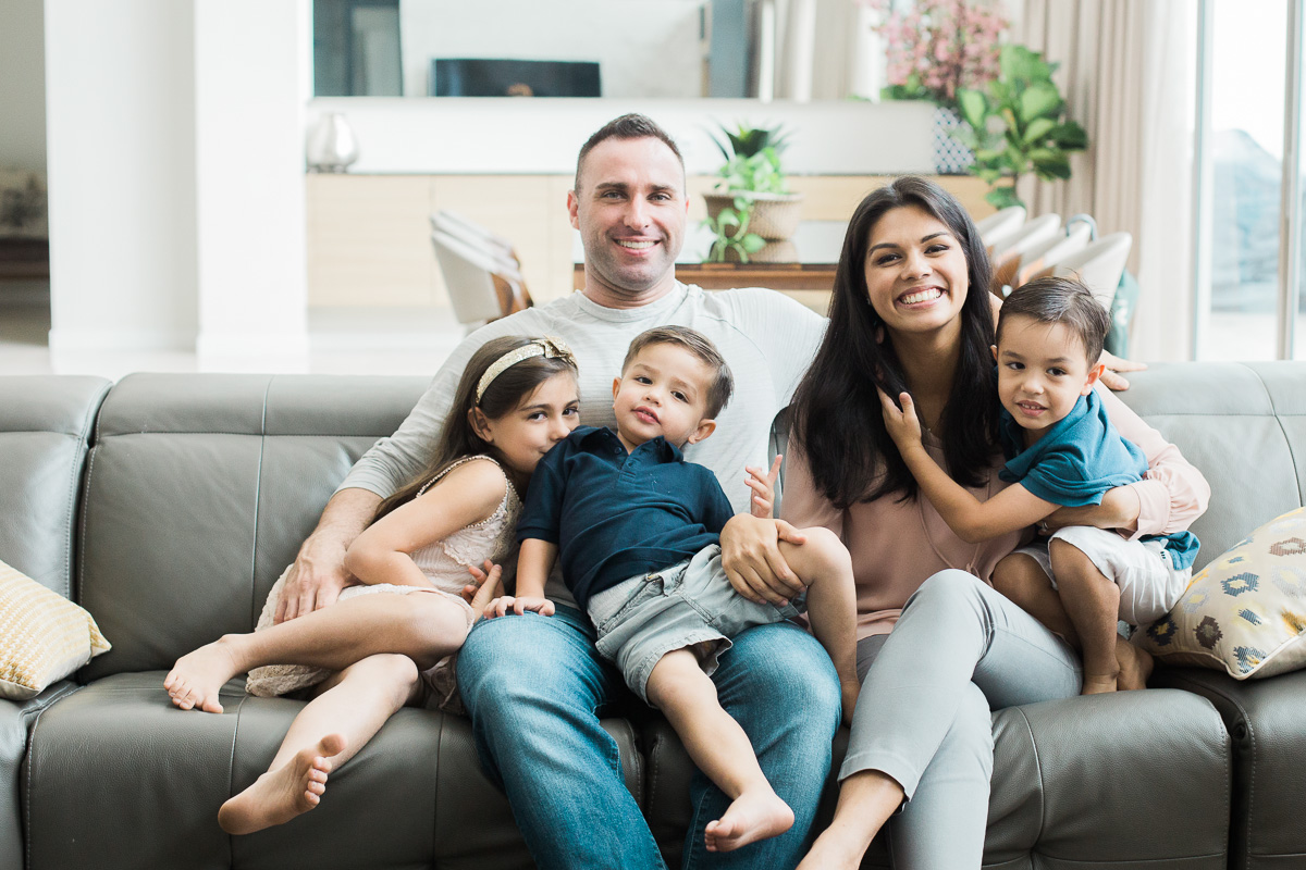 A family snuggles on the couch. A lifestyle image by kuala lumpur family photographer erica knecht