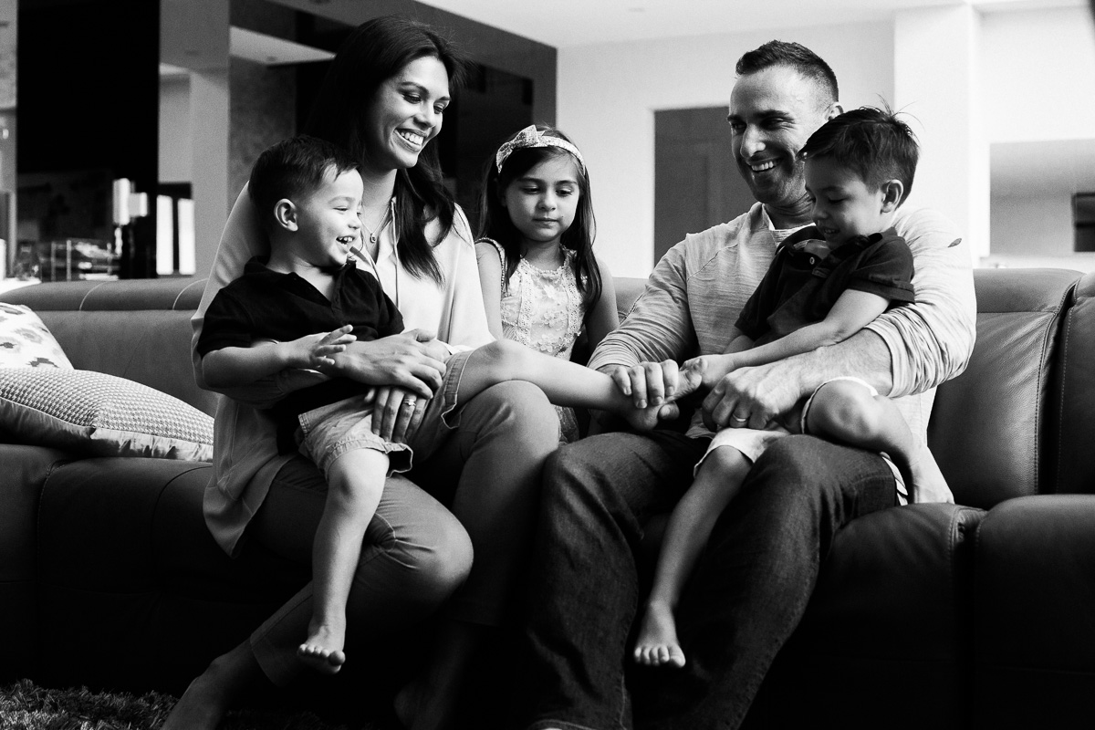 A family laughs and cuddles and tickles each other during a family photography session in Kuala Lumpur