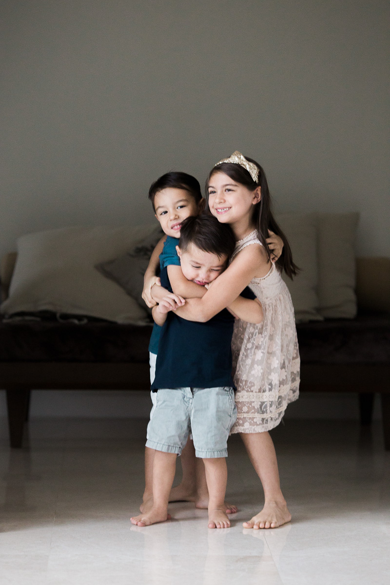 Three children cuddle / put each other in a headlock. A lifestyle family photography session in Kuala Lumpur, Malaysia.