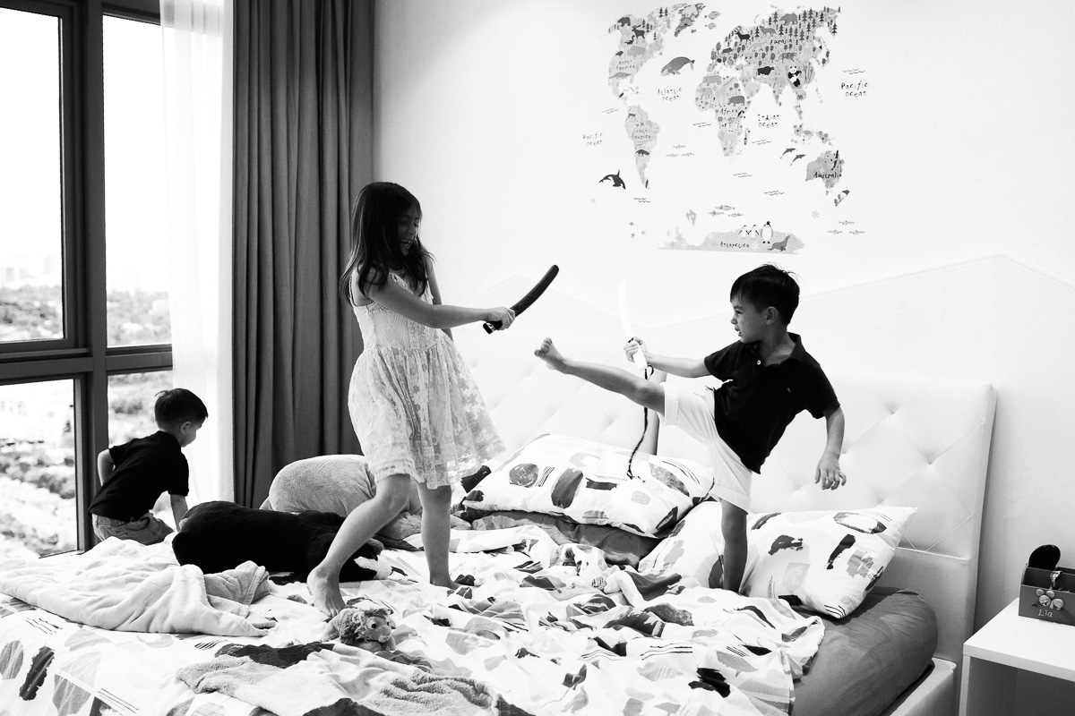 Three kids play swards. A black and white image by kuala lumpur family photographer Erica Knecht