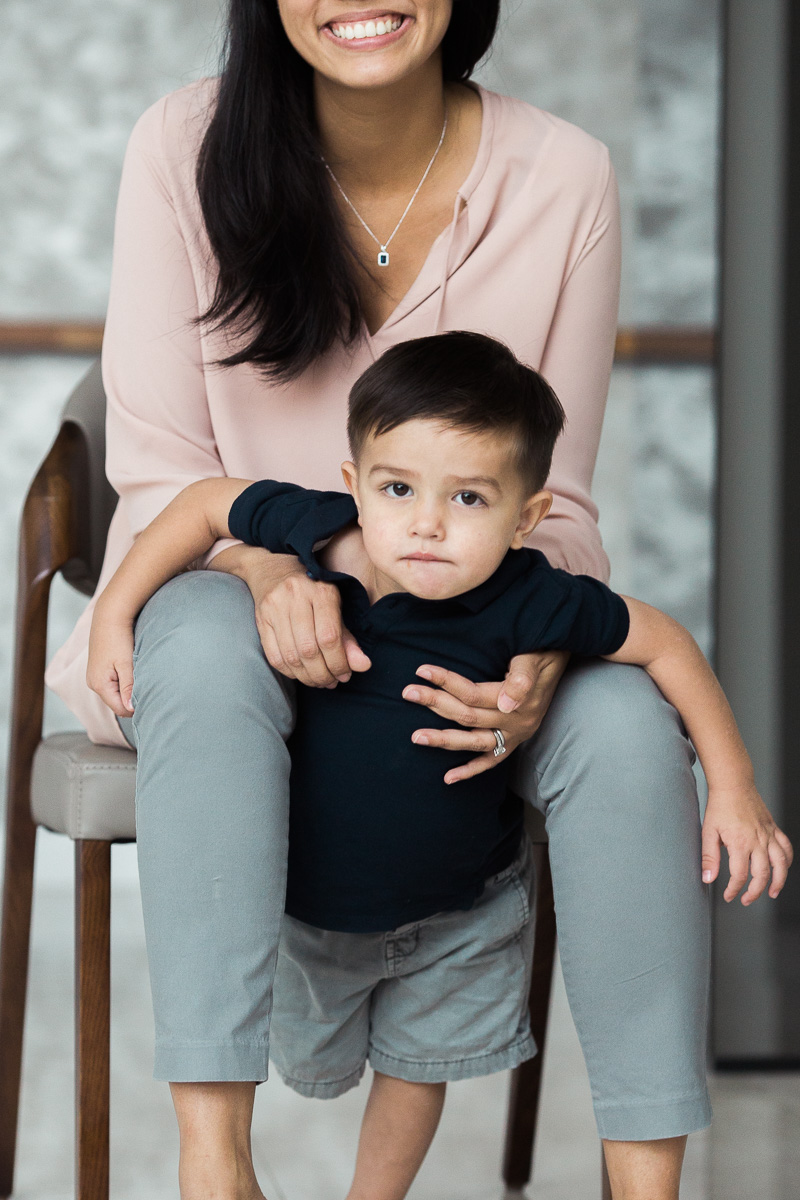 a mum sits on a chair and cuddles her son during a family photography session in Kuala Lumpur.