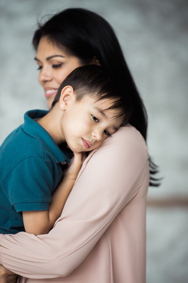 A mum clddles her son during a family photography session in kuala lumpur.