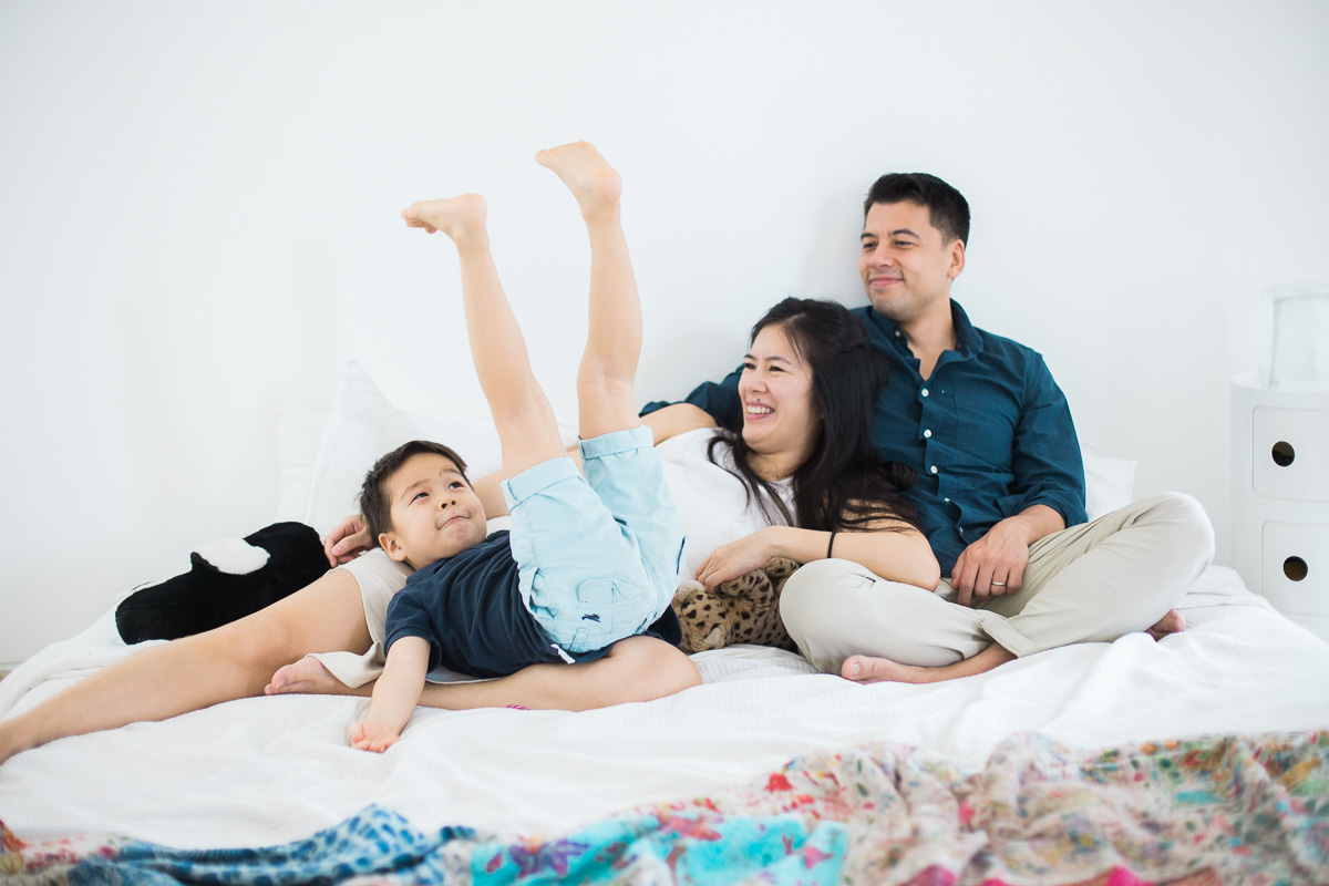 a family cuddle on bed in Jakarta, Indonesia. Photographed by Kuala Lumpur family photographer Erica Knecht