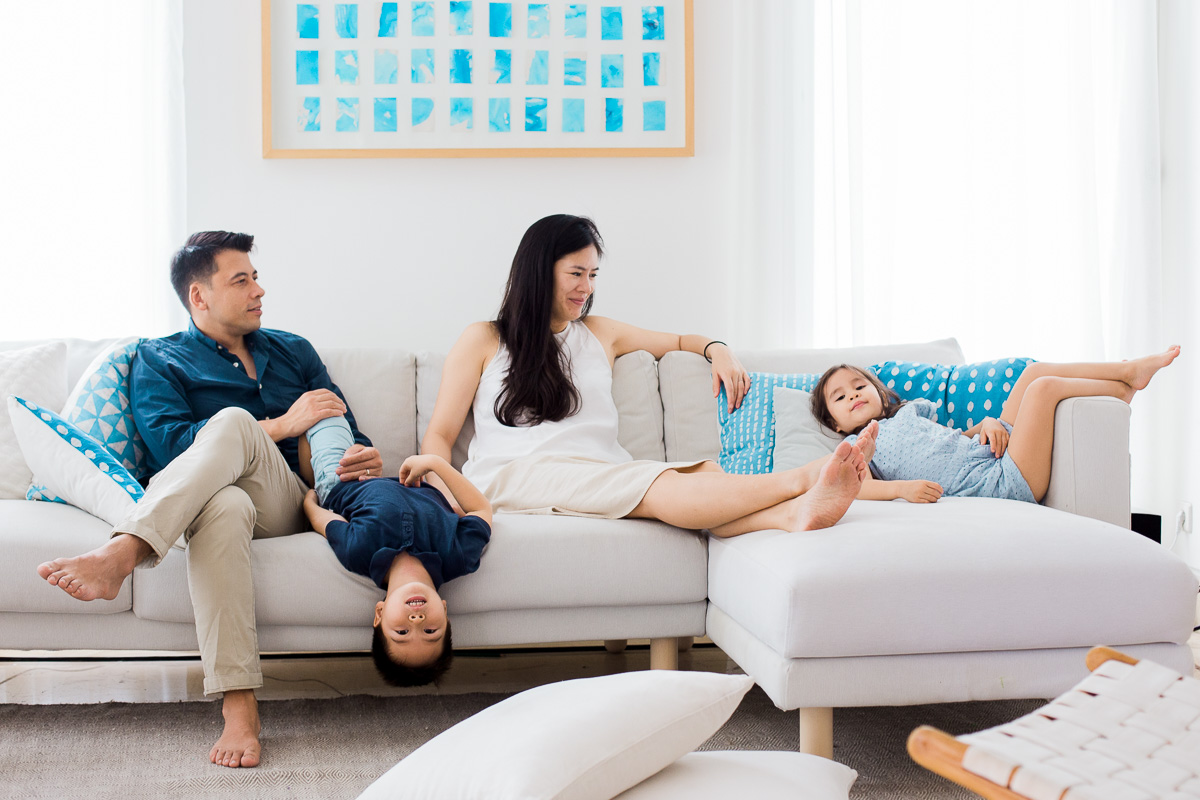a happy family hang out on their sofa in a beautifully styled room as captured by Kuala Lumpur based photographer Erica knecht